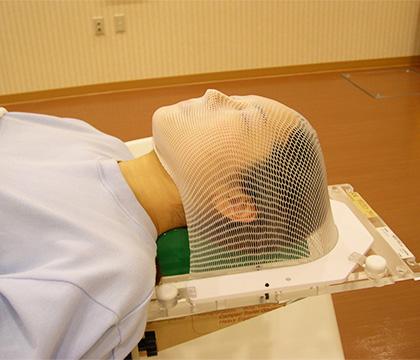 メッシュ状の顔の形に合わせたマスクで頭部を覆った状態